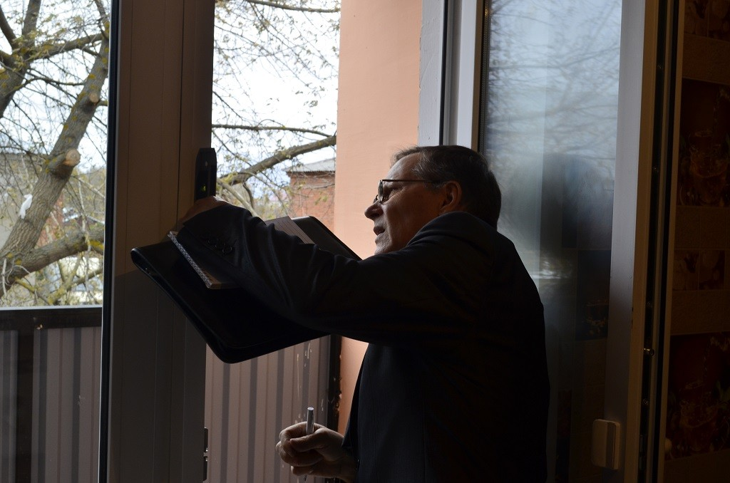 Эксперт регионального отделения ОНФ Анатолий Земцов проверяет качество установки пластиковых окон (фото Дмитрия Фирсова, газета «Маяк»)