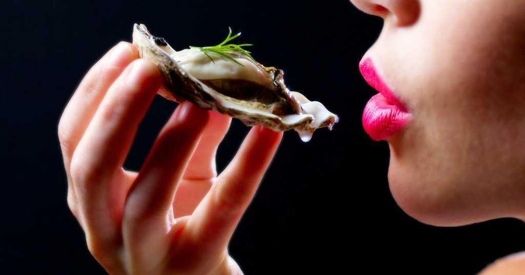 Девушка ест устрицу